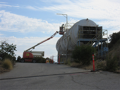 This photo shows a large white tank on the right side of a road. An individual is seen performing abatement activities in preparation for demolition of the tank.