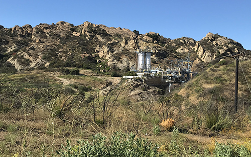 This photo shows the Bravo Test Stand in the background, with green vegetation flourishing in the foreground.